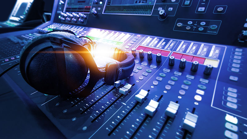 Professional audio studio sound mixer console board panel with recording , faders and adjusting knobs,TV equipment. Blue tone and close-up image with flare light effect.